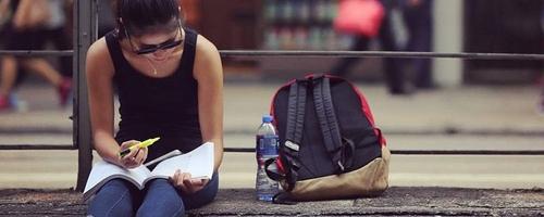 chica sentada en la acera viendo una libreta