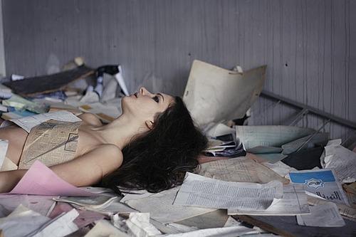 chica recostada en la cama con libros a su alrededor