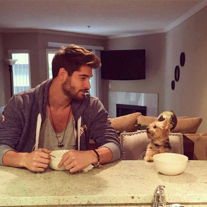 chico sentado en la mesa junto a su perro comiendo cereal