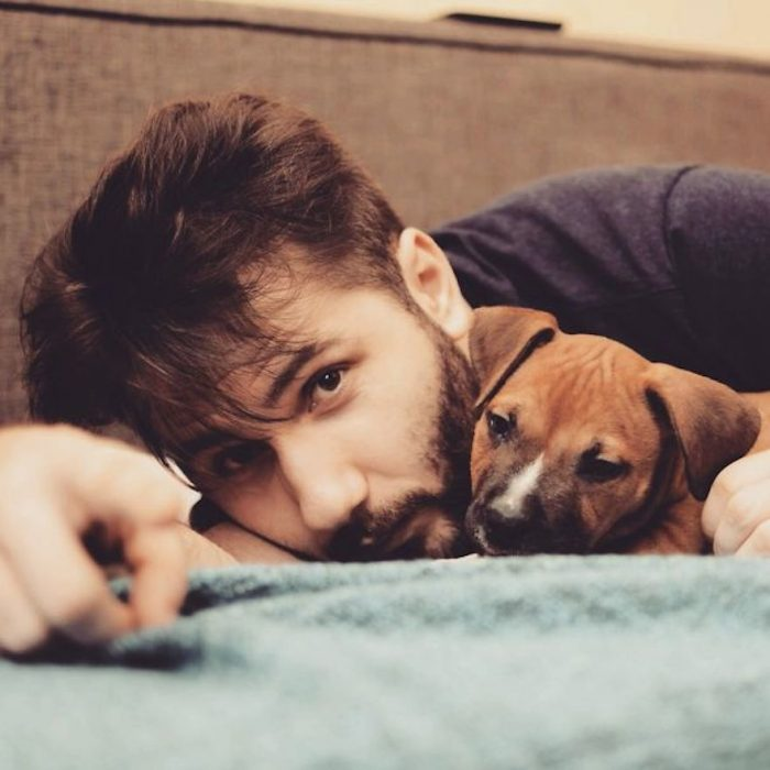 chico recostado con su perro en la cama