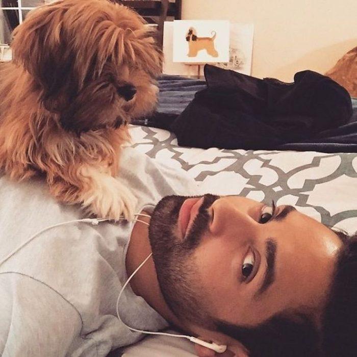 chico recostado en la cama escuchando música con su perro en el pecho