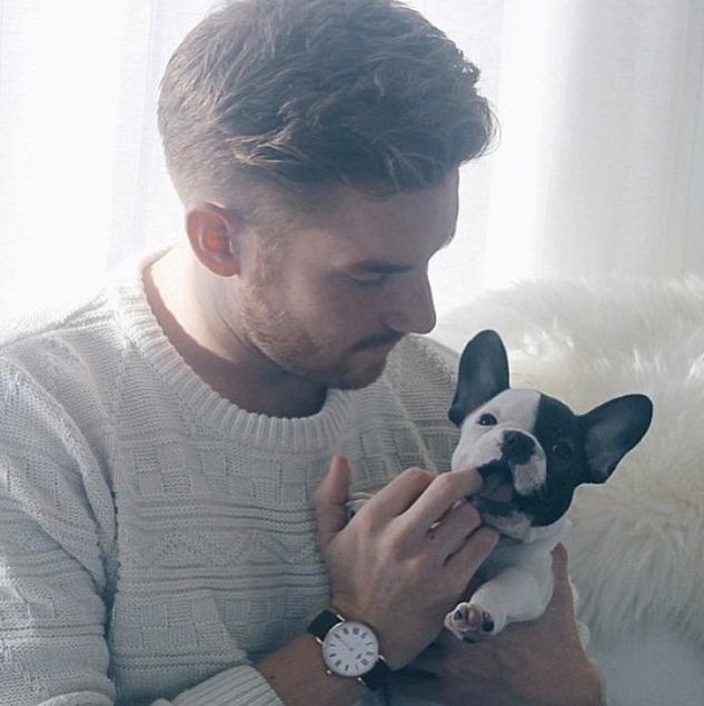 chico rubio con un suéter color claro sosteniendo a un perrito entre sus manos
