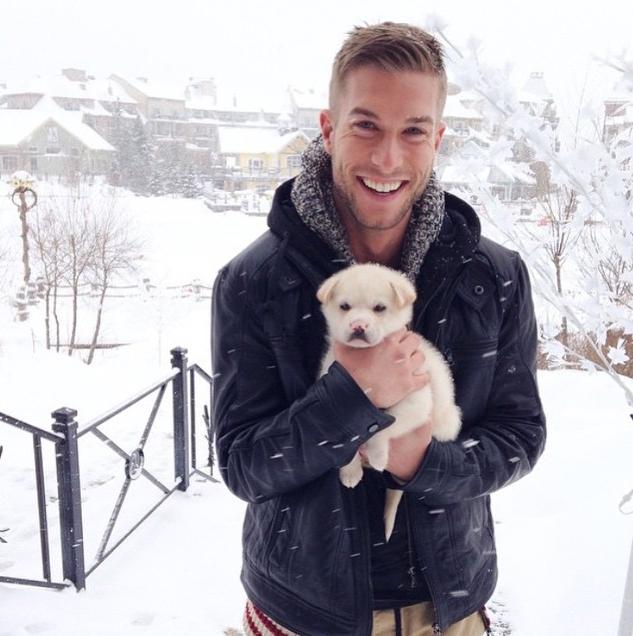 chico en medio de la nieve sosteniendo a un perro labrador