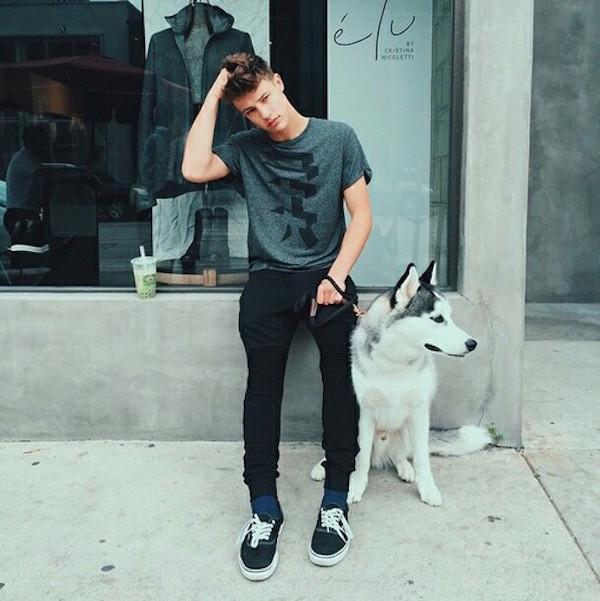 chico recargado sobre la pared de una tienda mientras sostiene a su perro con la correa