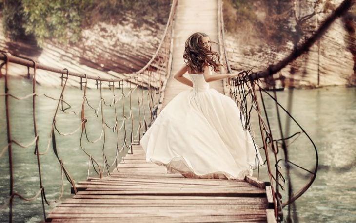 chica en vestido de novia corriendo sobre un puente