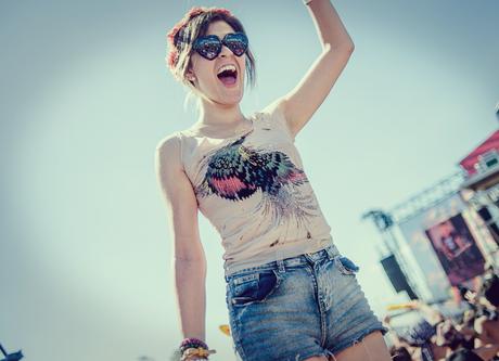 chica en un festival de música cantando y riendo