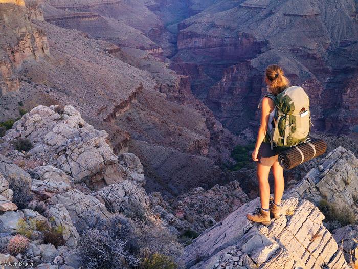 chica con una maleta de viaje parada sobre unas rocas