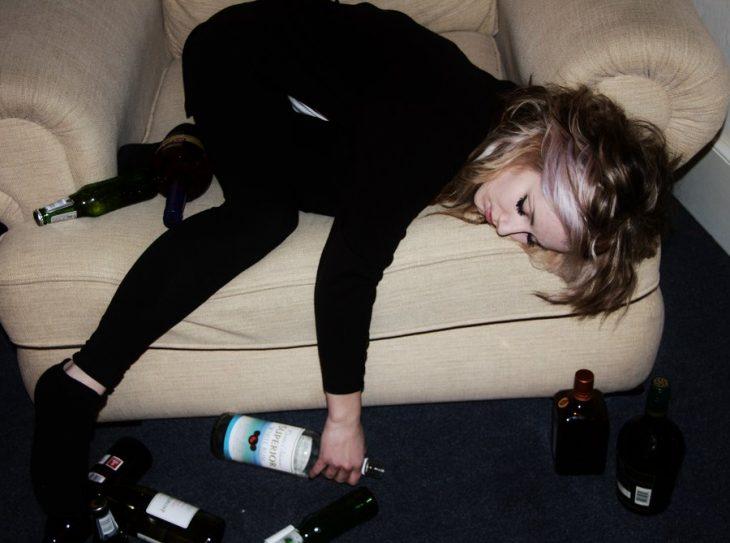 Chica dormida en un sillón rodeada de botellas