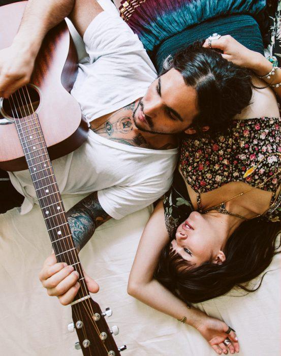pareja acostados mientras él toca la guitarra