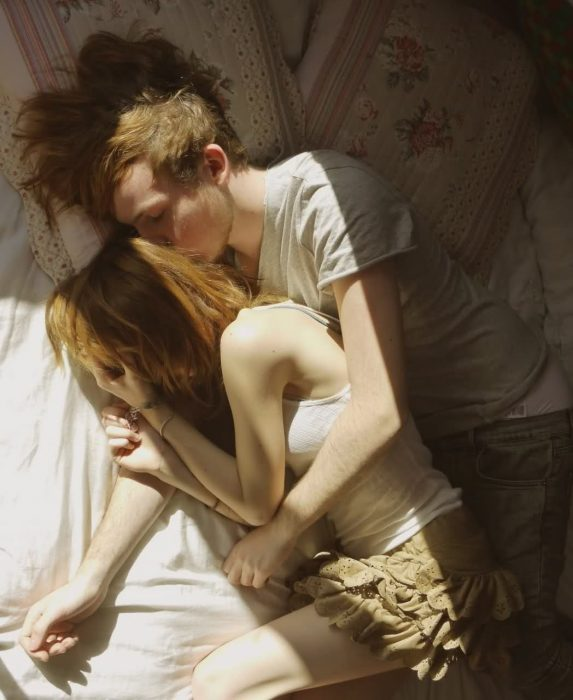 chica abrazada a un chico mientras ambos están recostados en la cama