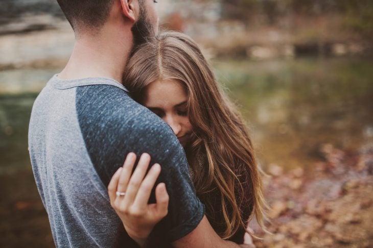 chica abrazando a un chico al lado de una laguna