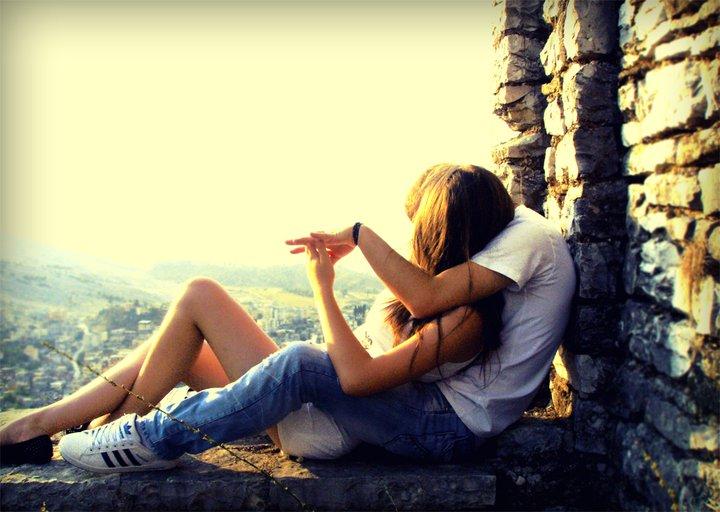 pareja de novios abrazados y sentados viendo el atardecer
