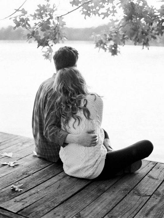 pareja de novios sentados en un muelle abrazados