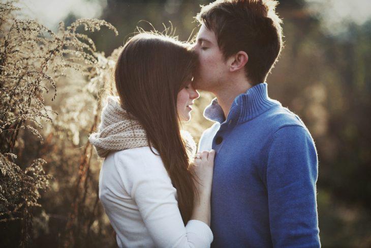 hombre besando a su novia en la frente mientras estan paados en medio de un campo