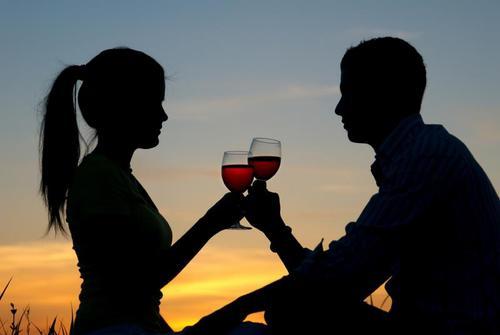pareja de novios sentados tomando vino viendo el atardecer