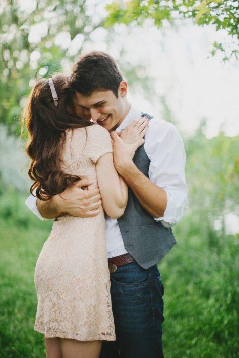 pareja de novios abrazados parados en medio de un jardín