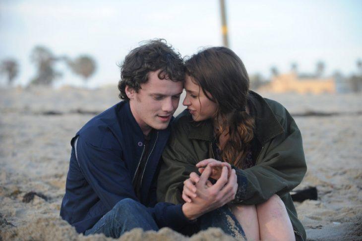 escena de la película like a crazy protagonistas sentados en la playa conversando