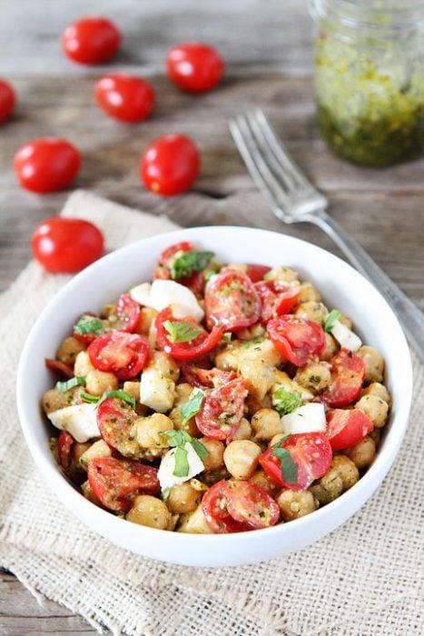 Ensalada de garbanzos tomate y queso servidas en un tazón sobre una mesa listas para comer