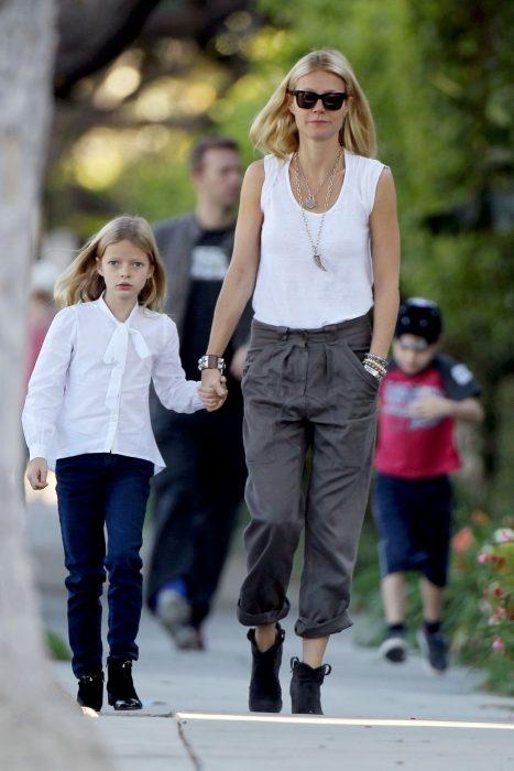 actriz caminando de la mano de su pequeña hija por la calle