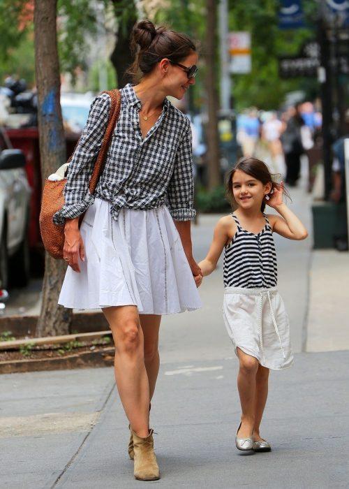 Katie Holmes y su hija suri caminando por las calles tomadas de las manos y vestidas similar con faltas y blusa negra de rayas