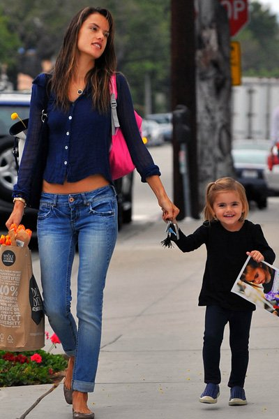 Famosa modelo de la mano con su hija caminando por la calle