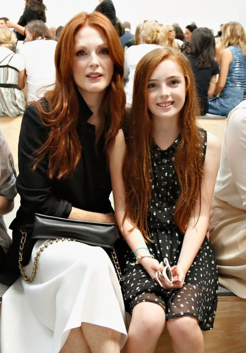 Actriz de hollywood sentada junto a su hija que tiene el cabello rojo al igual que ella