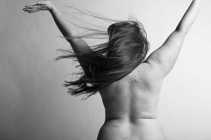 mujer parada dando la espalda y alzando sus brazos sobre su cabeza