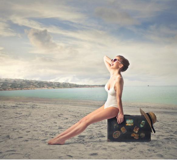 Chica sentada sobre un maleta en la playa