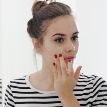 Chica aplicándose maquillaje en el rostro