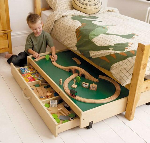 cama de un niño que bajo ella tiene un cajón con una pista de carreras y otro cajón más para guardar juguetes