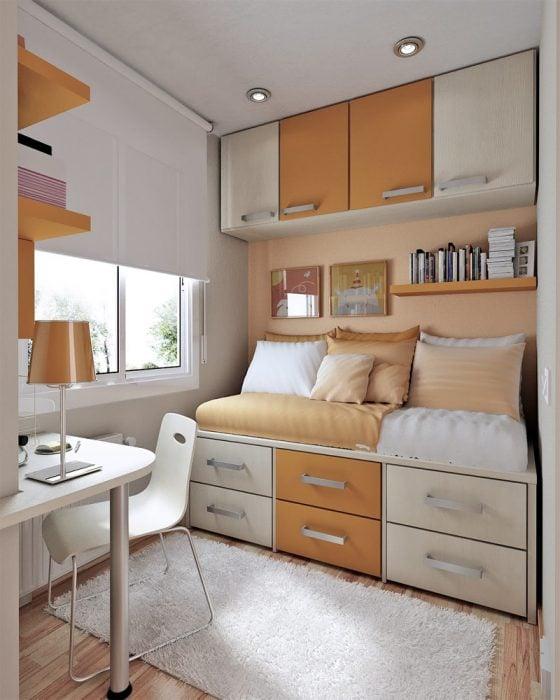 habitación donde la cama esta pegada a la pared y sobre ella tiene estantes para colocar libros y frente a ella tiene un escritorio con lamparas
