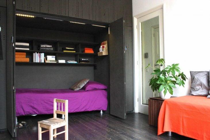 cama que se encuentra de un armario que ademas en la parte superior contiene libros