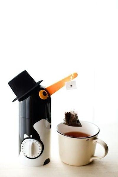 pinguino que sostiene un infusor de té