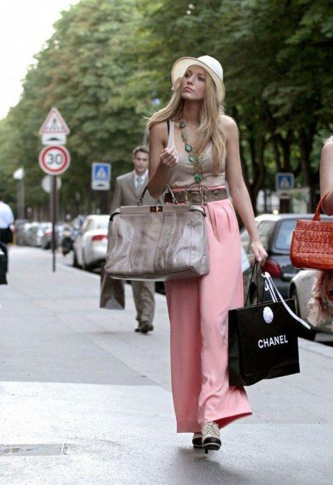 chica caminando por la calle con bolsas en las manos