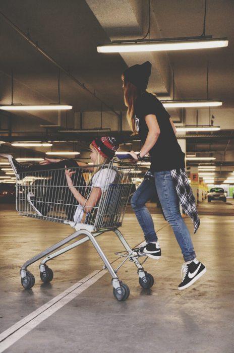 chica sobre un carrito de super mercado y otra empujándola