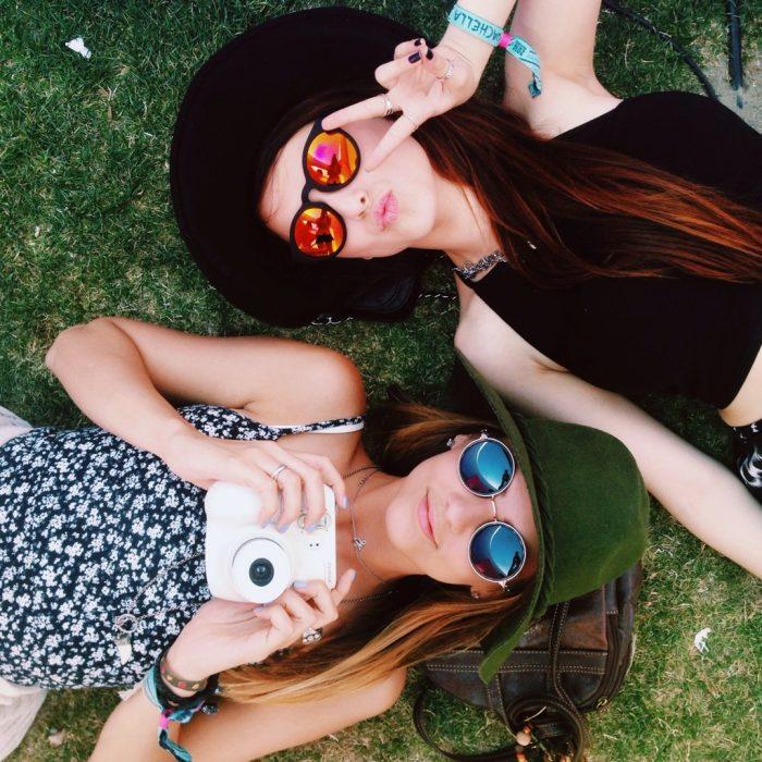 chicas recostadas en el pasto tomándose fotos