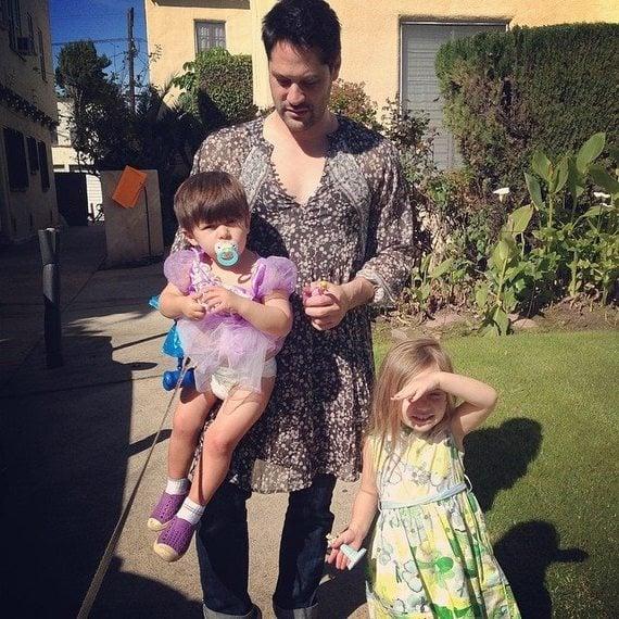 papá usando un vestido y sacando a pasear a sus hijos