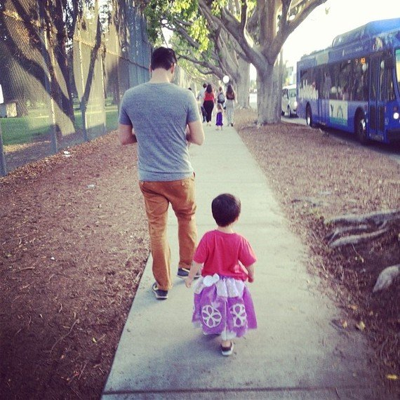 niño con vestido siguiendo a su papá por la calle