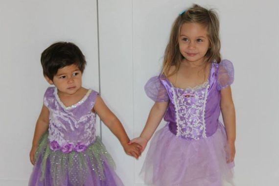 hermanos usando un vestido de color morado tomados de las manos y recargados en la pared