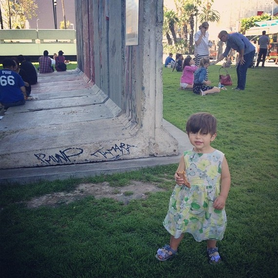 niño usando un vestido y parado en un parque mientras le toman una foto
