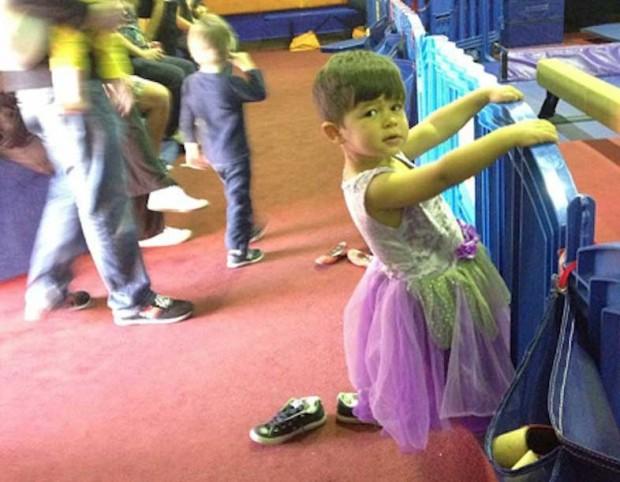 niño usando un vestido de color morado con verde y deteniendose de una barandilla