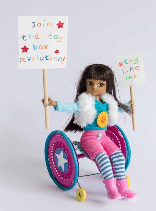 Muñeca que esta sentada en una silla de ruedas con carteles de propuesta