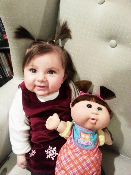niña sentada a su muñeca que luce de manera similar a ella