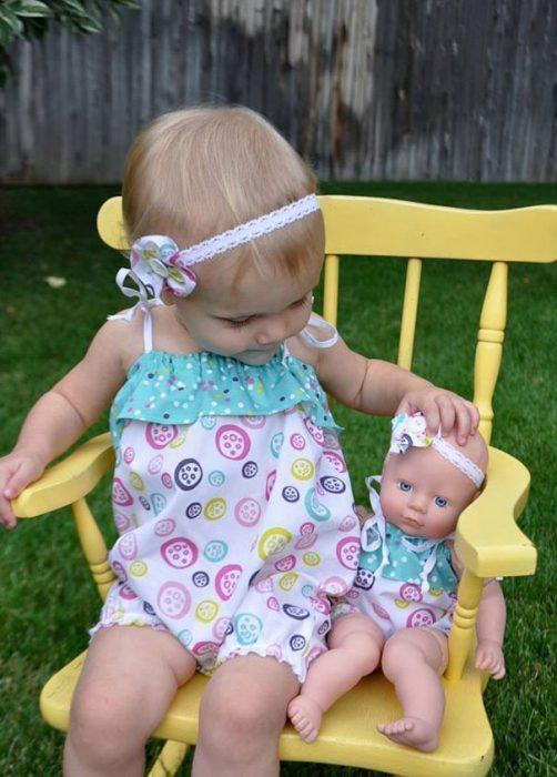 niña sentada en una silla junto a su muñeca vestidas de la misma manera