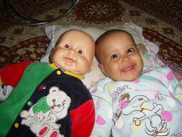 niño recostado en la cama junto a su muñeco que luce exactamente igual a él