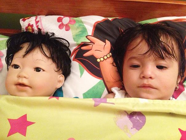bebe acostada junto a su muñeca en la cama