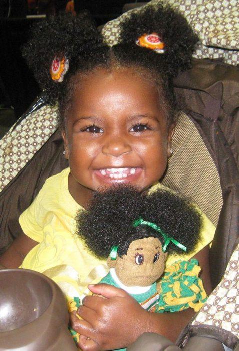 Niña con su muñeca en los brazos sentadas en un sofá