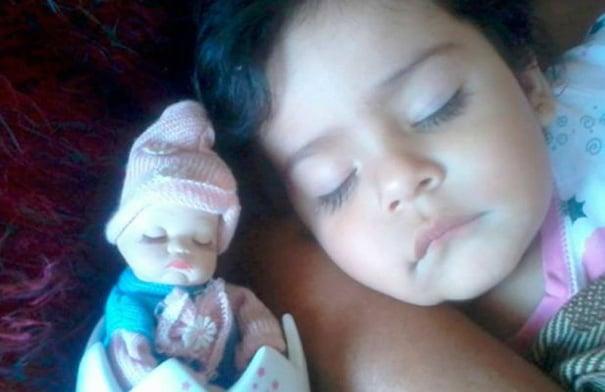 bebe dormida junto a su muñeca que es casi como ella