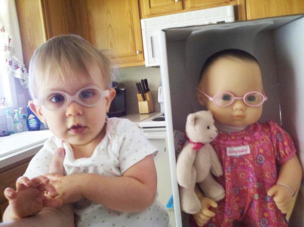 bebe con lentes que esta parada a una muñeca que se ve similar a ella