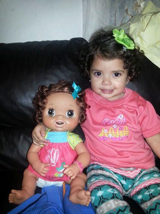 bebe sentada junto a su muñeca a la que se parece